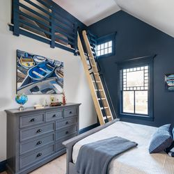 """Removing a small attic created overhead space in the son's bedroom for a loft play or sleepover space. A window placed up high boosts daylight. <em>Bedding: </em><a class=""""ql-link"""" href=""""https://creativethreadsusa.com/"""" target=""""_blank""""><em>Creative Threads</em></a><em>; Artwork: </em><a class=""""ql-link"""" href=""""https://www.southcountyart.org/"""" target=""""_blank""""><em>South County Art Association</em></a>"""