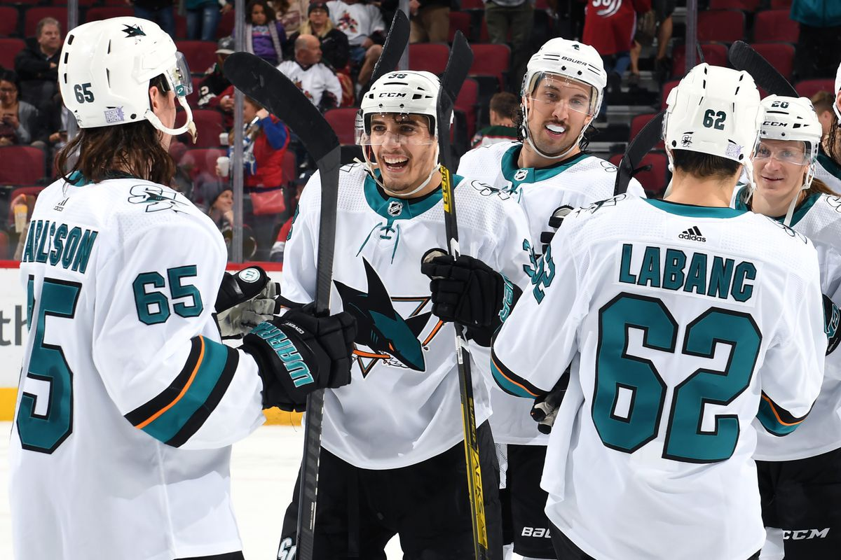 Mario Ferraro #38 of the San Jose Sharks is congratulated by Erik Karlsson #65, Kevin LaBanc #62 and teammates following a 4-2 victory against the Arizona Coyotes during the NHL game at Gila River Arena on November 30, 2019 in Glendale, Arizona.