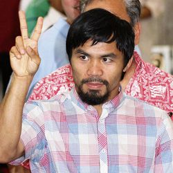 FILE - In this June 16, 2012, file photo, former welterweight world champion Manny Pacquiao flashes the sign of peace during a Mass in Manila, Philippines. Champion boxers Floyd Mayweather Jr. and Pacquiao have reached a confidential settlement Tuesday, Sept. 25, 2012, in their federal defamation case in Las Vegas. Attorneys for all sides say the terms won't be disclosed.
