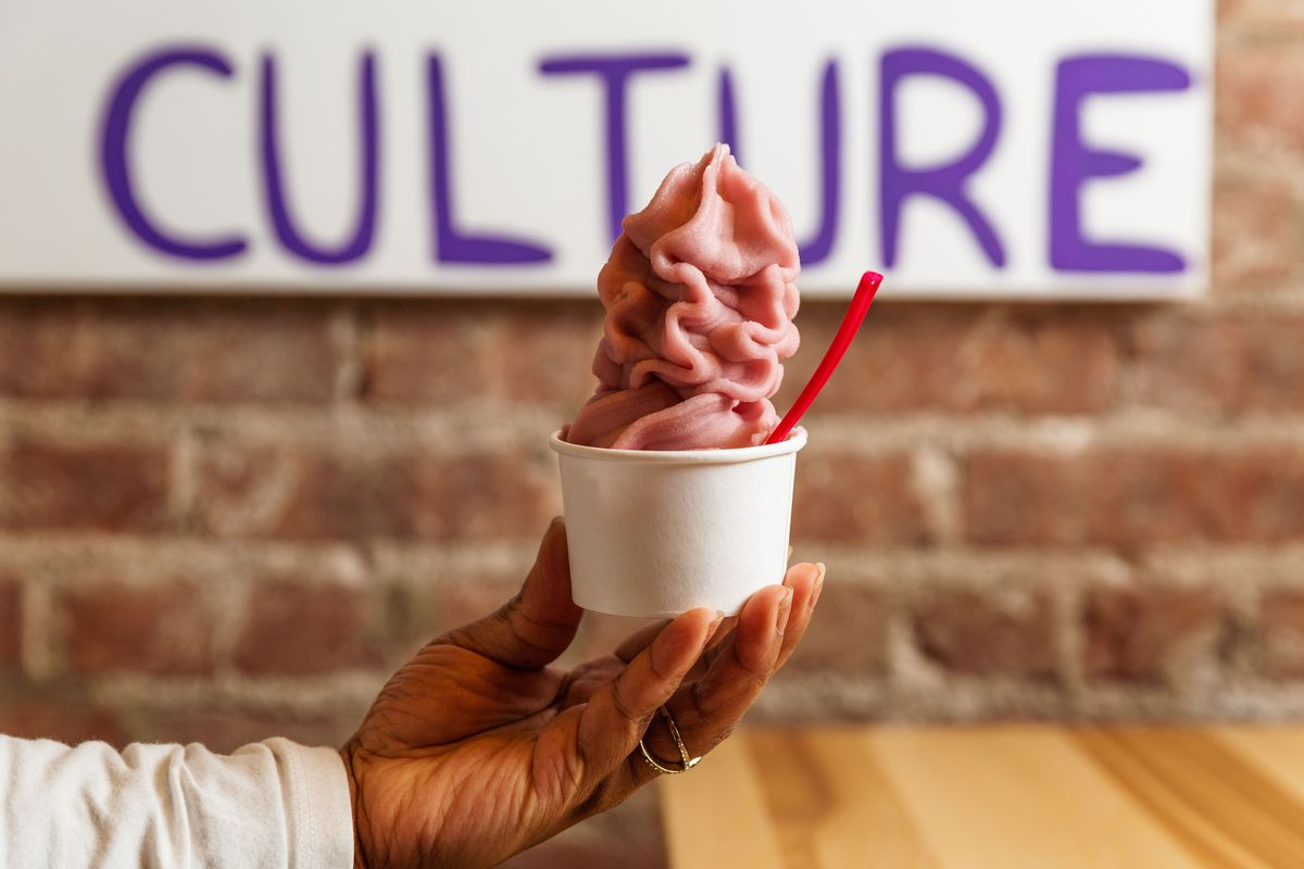 A diner holds a cup of rice milk hibiscus raspberry soft serve over a blonde wood table