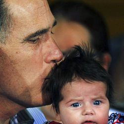 Republican presidential candidate, former Massachusetts Gov. Mitt Romney kisses an unidentified baby as he makes a campaign stop at Thompson Tractor, Friday, March 9, 2012, in Tarrant, Ala., near Birmingham.