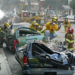 Rescue workers remove bricks from crushed cars near the remains of a collapsed two-story building in Paso Robles, Calif., following an earthquake Dec. 22, 2003.