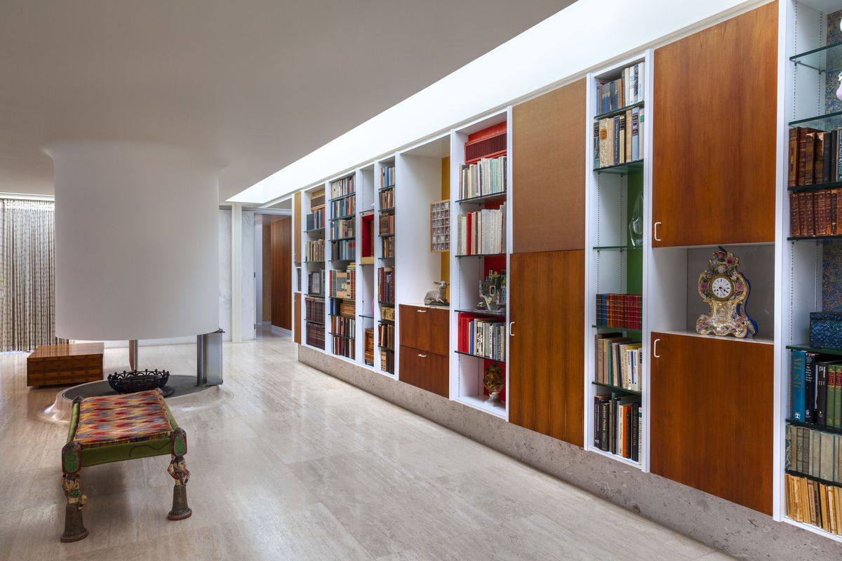A long wall stretches across the entire back side of a room that is built out with wood cabinet doors and open shelving holding books and art. A white tubular fireplace is suspended from the ceiling in the middle of a beige stone floor.
