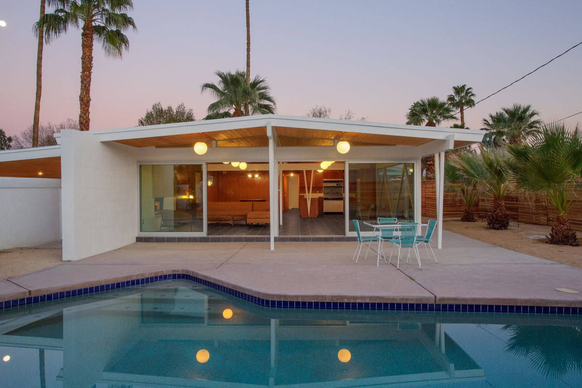 An exterior view of the back of the house at sunset. There is a pool in the foreground, a patio with an outdoor dining table, and views into the living room.
