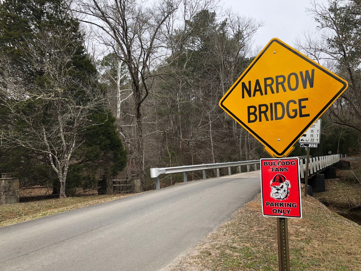 """A sign near a bridge in Chubbtown, Georgia, reads """"Narrow Crossing."""" Beneath it is a small sign reading """"Bulldog Fanss Parking Only."""""""