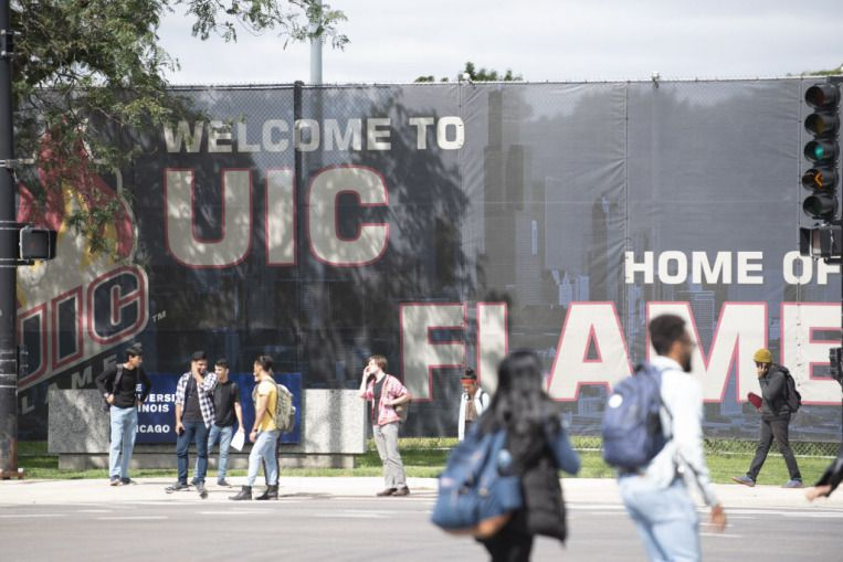 Pedestrians walk past signage for the University of Illinois at Chicago campus in Chicago on September 10, 2018.   Colin Boyle/Sun-Times