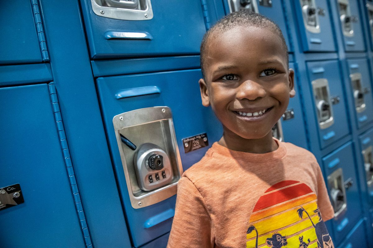 Morghan Hampton, 4, a pre-kindergarten student at Avondale Meadows YMCA Early Learning Center, smiles next to a set of lockers on Tuesday, April 30, 2019.