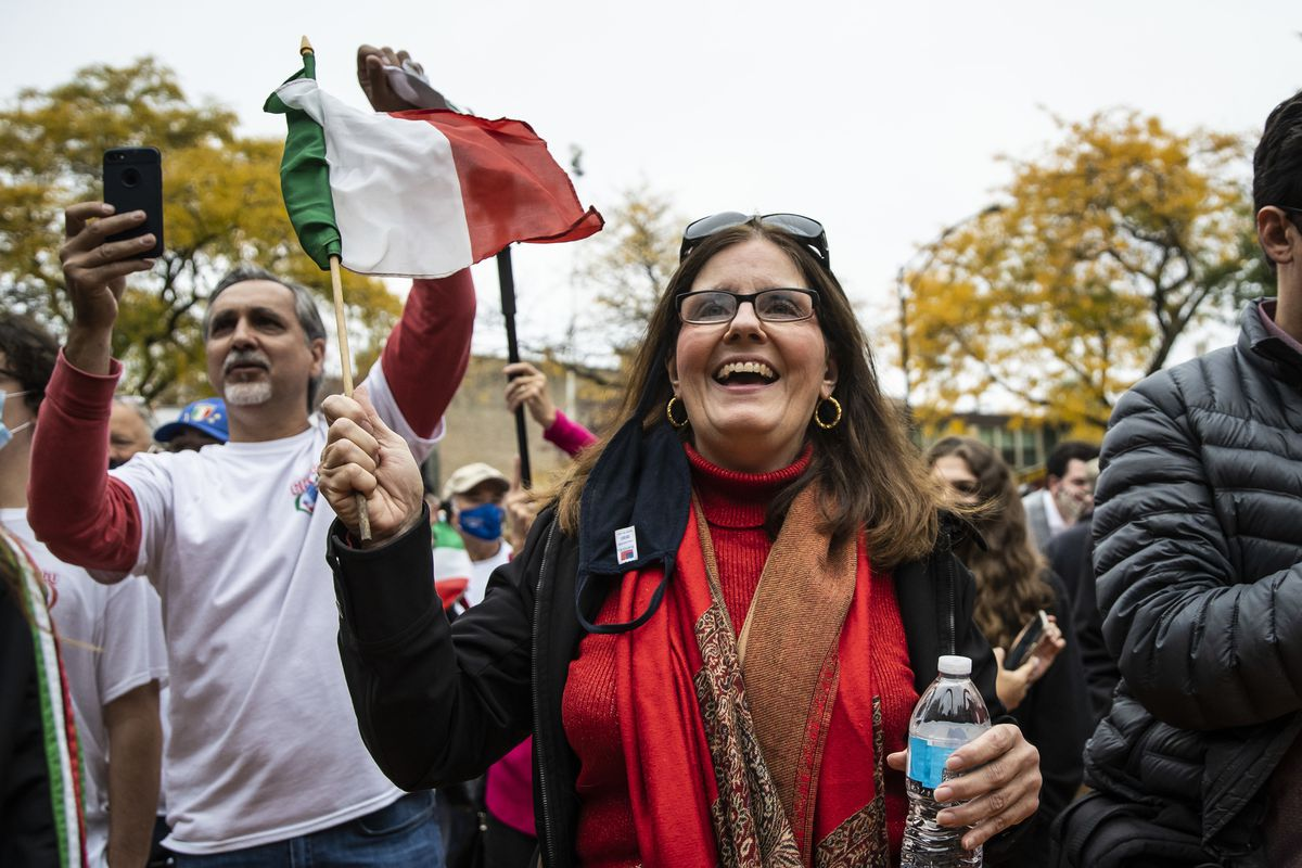 Beth Ann Iosco-Tarallo, 59, of Melrose Park, waves an Italian flag during the Columbus Day: Italian American Heritage Celebration at Arrigo Park in the Little Italy neighborhood, Monday morning, Oct. 12, 2020.