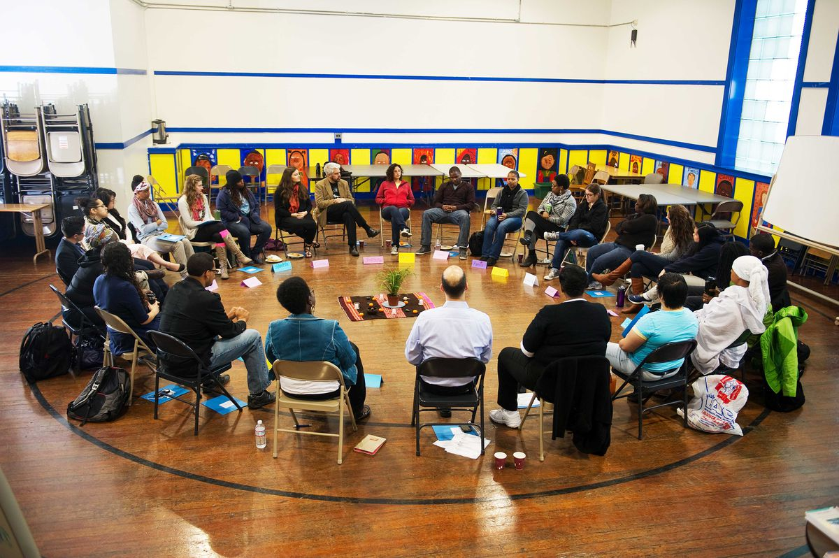 Educators and administrators sit in a circle in an auditorium.
