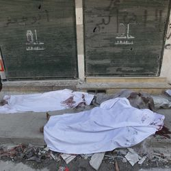 A Free Syrian Army soldier, left, looks at dead bodies laying on a roadside in front of al-Shifa hospital, at al-Shaar neighborhood, in Aleppo city, Syria, Monday Sept. 24, 2012. Syrian warplanes bombed two buildings on Monday in the northern city of Aleppo, killing at least five people including three children from the same family, activists said.
