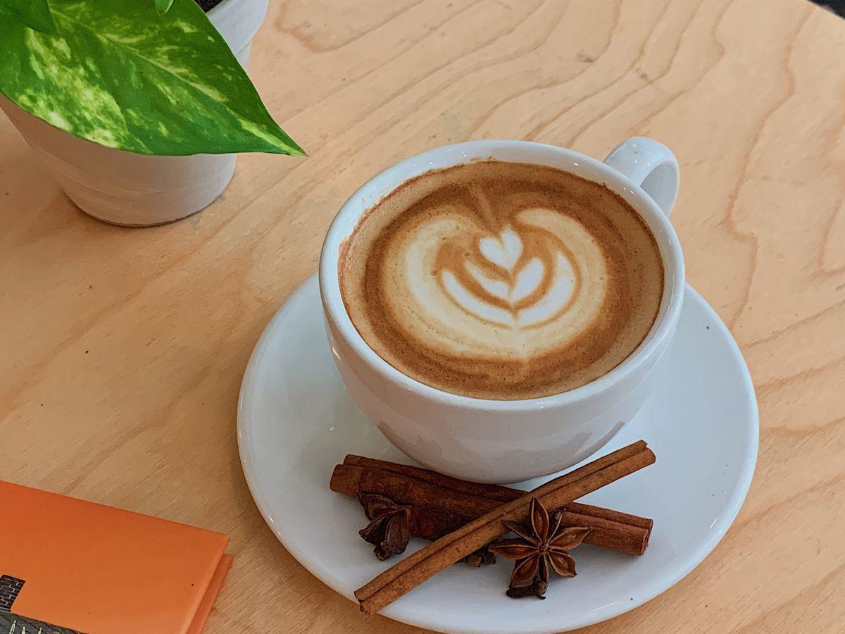 A pumpkin latte in a white ceramic coffee cup.