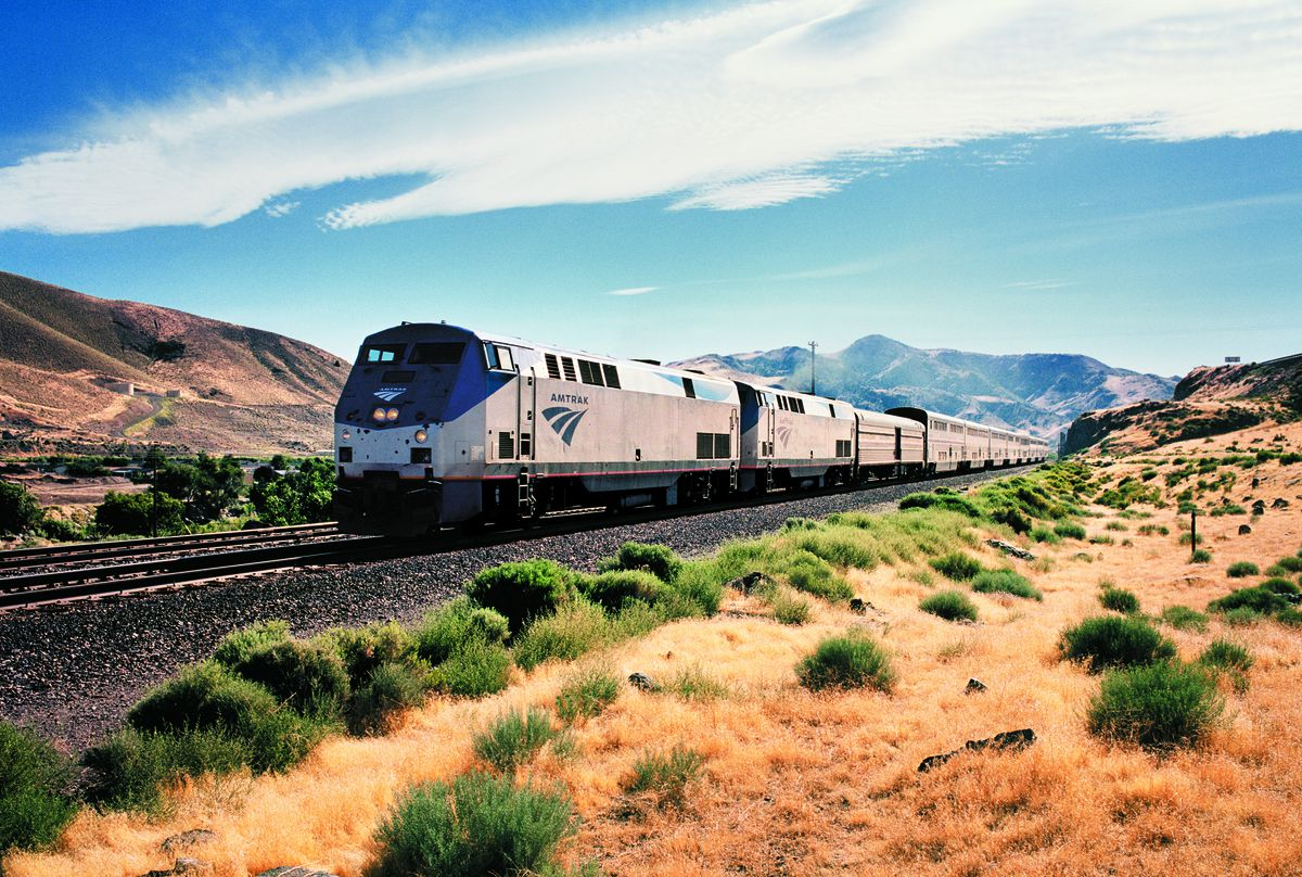 A train rides along a track through a desert with tiny shrubs dotting the landscape. There are mountains in the distance.