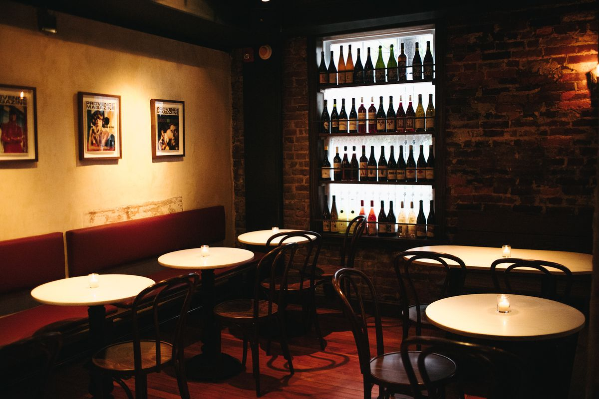 a wine bar with exposed brick walls and wine on shelves