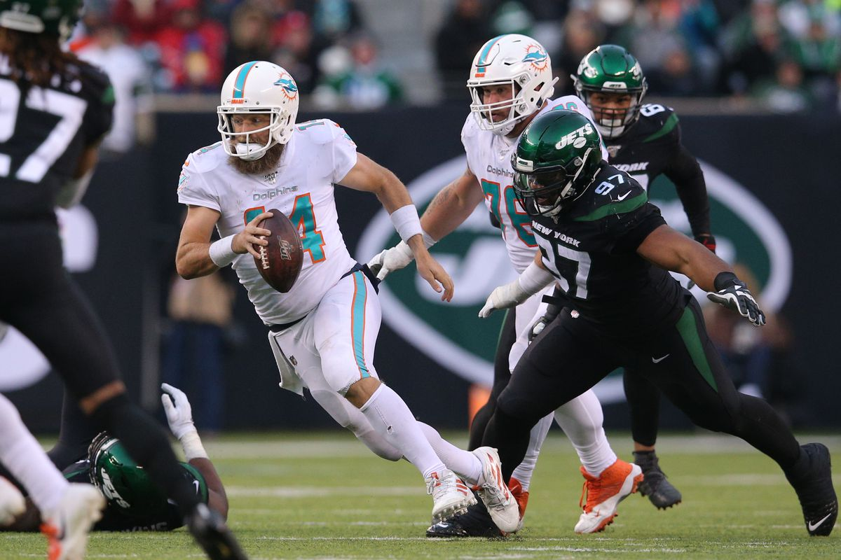 Miami Dolphins quarterback Ryan Fitzpatrick runs the ball against New York Jets defensive tackle Nathan Shepherd during the fourth quarter at MetLife Stadium.