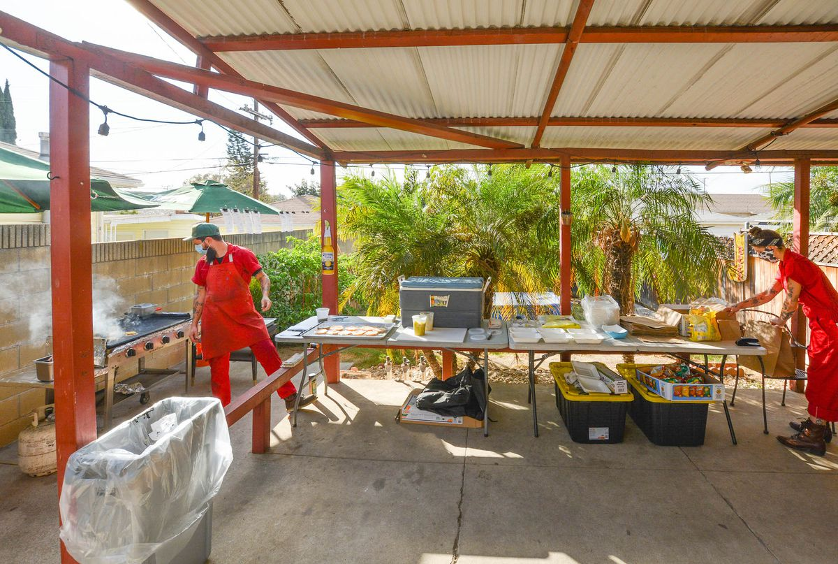 Two people in red jumpsuits work a griddle and make orders at a back yard pop up.