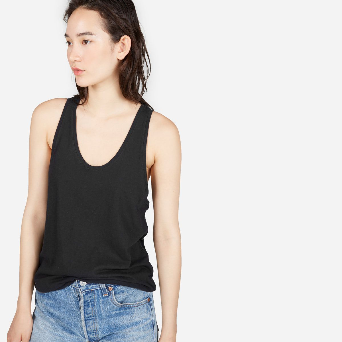A model in a black tank top and jeans