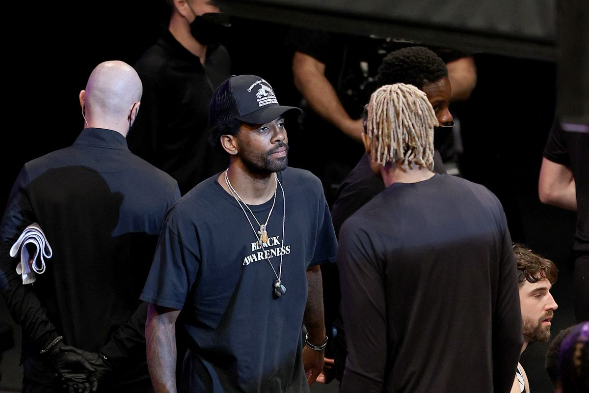 Kyrie Irving #11 of the Brooklyn Nets supports his teammates from the bench in the third quarter against the Milwaukee Bucks during game seven of the Eastern Conference second round at Barclays Center on June 19, 2021 in the Brooklyn borough of New York City.