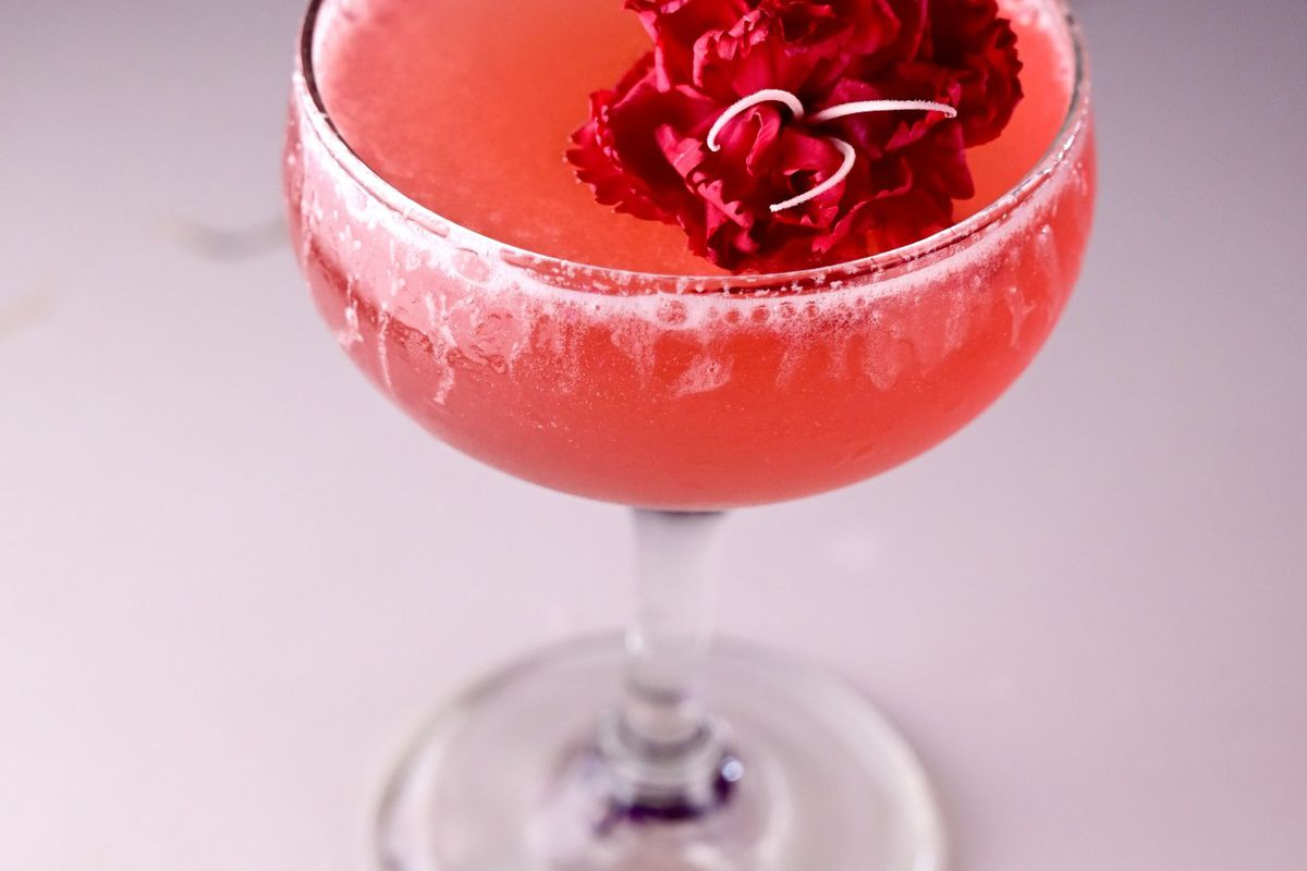 a pink cocktail with that looks like flower petals as a garnish