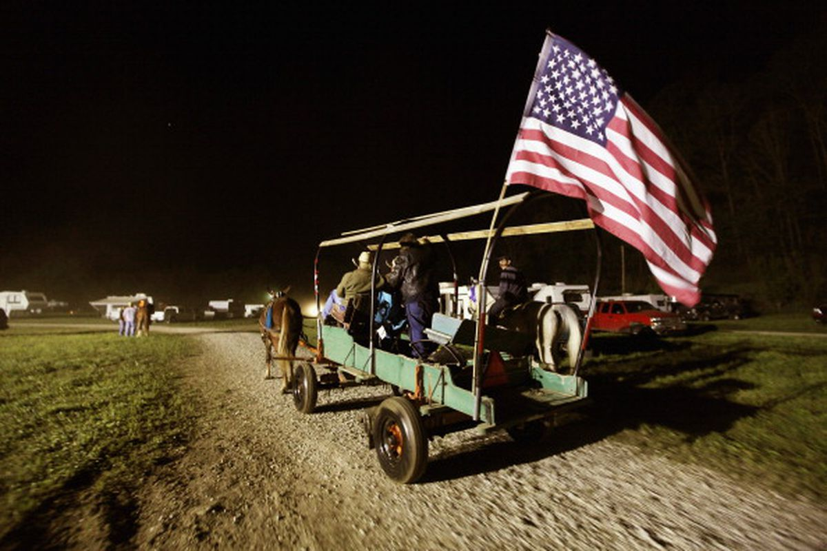 Riders pass in a wagon with an American flag at the Owsley County Saddle Club trail ride on April 19, 2012, in Booneville, Kentucky. The 2010 US Census listed Owsley County as having the lowest median household income in the country outside of Puerto Rico
