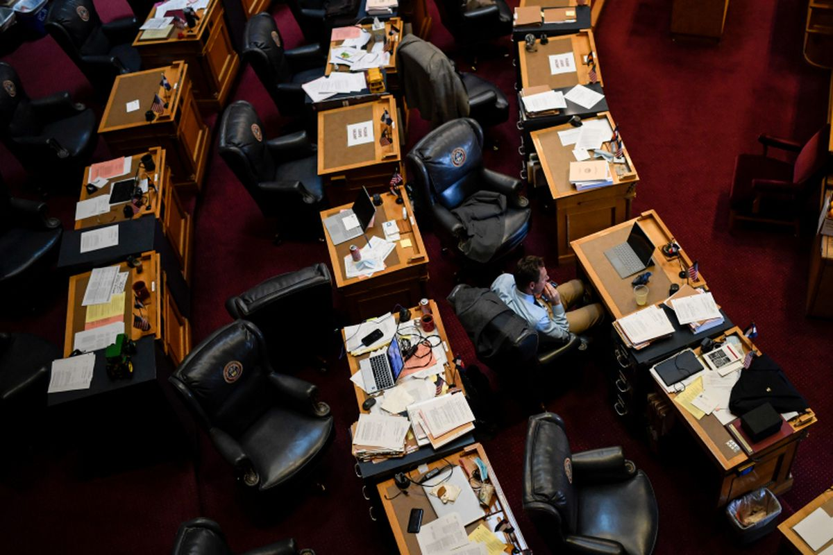 Sen. Jim Smallwood sits alone amid desks, many cluttered with papers, lined up in a semicircle in legislative chambers at the Colorado State Capitol