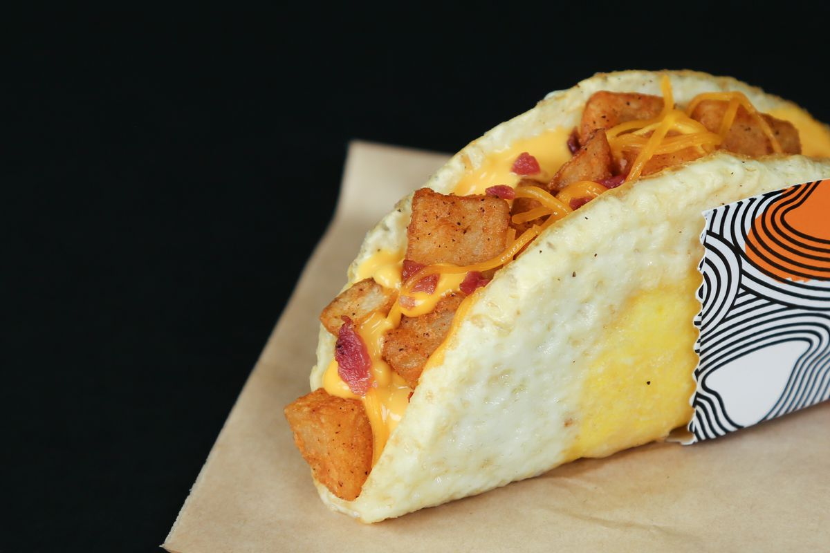 The naked egg taco, topped with browned potatoes and shredded cheese, on a blond wood table with a black background.