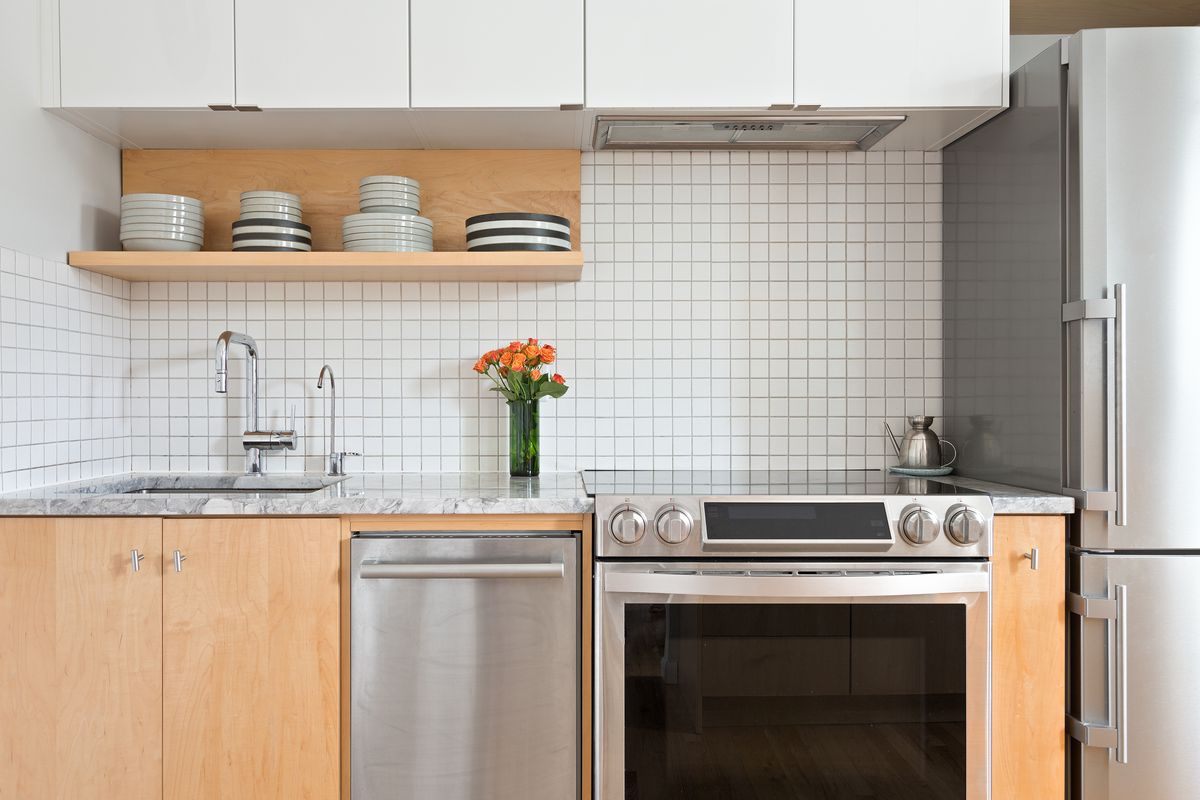 A kitchen with white tile backsplash, floating shelves, and stone counters.