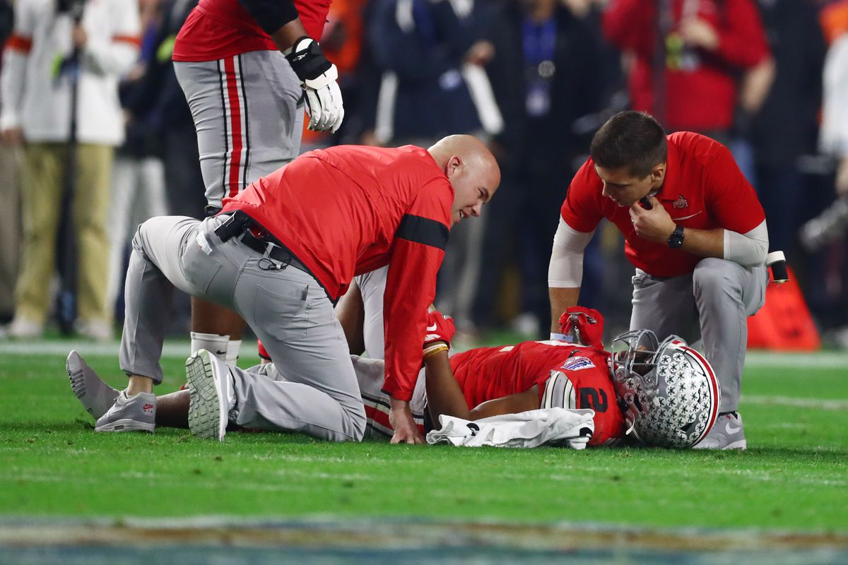 Ohio State Buckeyes running back J.K. Dobbins is checked on after an apparent injury against the Clemson Tigers during the first half in the 2019 Fiesta Bowl college football playoff semifinal game at State Farm Stadium.