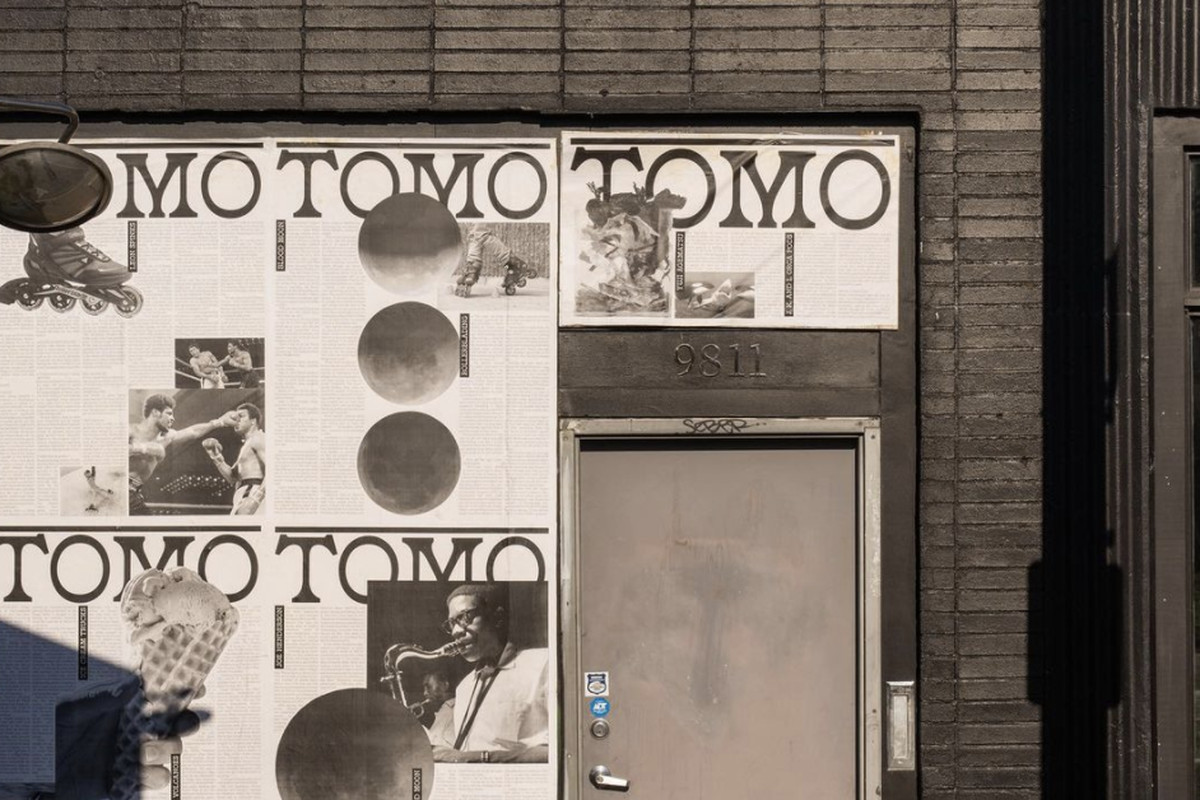 The exterior of Tomo in White Center, with the restaurant's name plastered on the wall as black-and-white vintage posters
