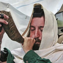 A religious Jewish man blow a ram's horn, normally sounded during Jewish rituals, at the tomb of Rabbi Nachman, the great grandson of the founder of Hasidism, in the town of Uman, 200 kilometers (125 miles) south of Ukraine's capital Kiev, Thursday, Sept. 17, 2009. Thousands of Hasidic Jews from around the world gathered in Uman to mark the Jewish New Year, or Rosh Hashana, at Nachman's tomb. (AP Photo/Efrem Lukatsky)