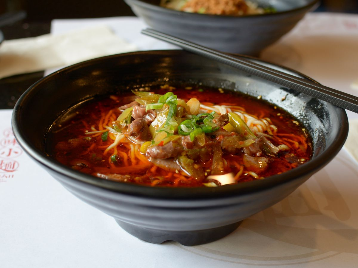 Mian, a Chinese spicy noodle spot, shows a black bowl with lots of chili-infused red liquid inside.
