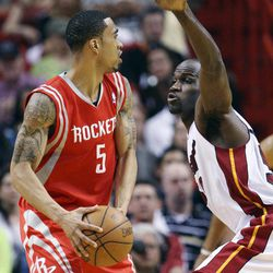 Houston Rockets guard Courtney Lee (5) looks for an open teammate past Miami Heat center Joel Anthony during the first half of an NBA basketball game, Sunday, April 22, 2012, in Miami.