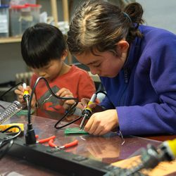 Kids learn to solder during an open lab put on by Curiosity Hacked.
