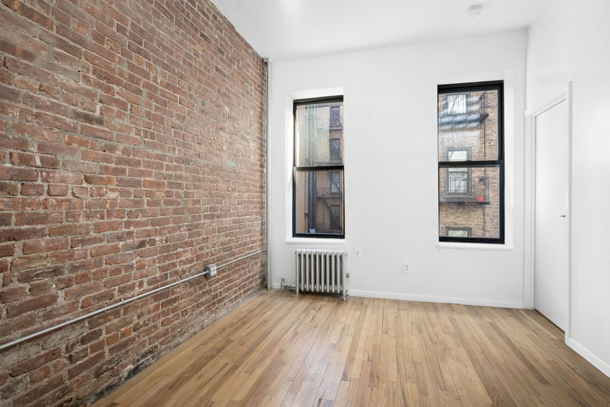 A bedroom with exposed brick, two windows, white walls, and hardwood floors.