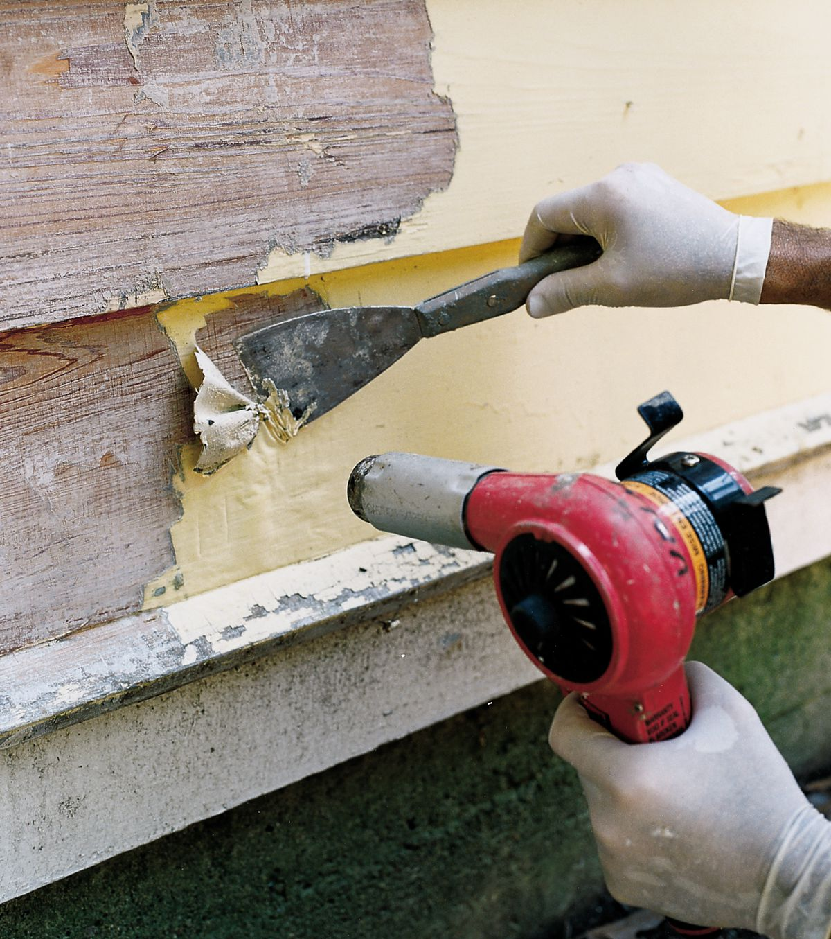 Man Uses Heat Gun and Chisel To Scrape Off Old Paint Off House