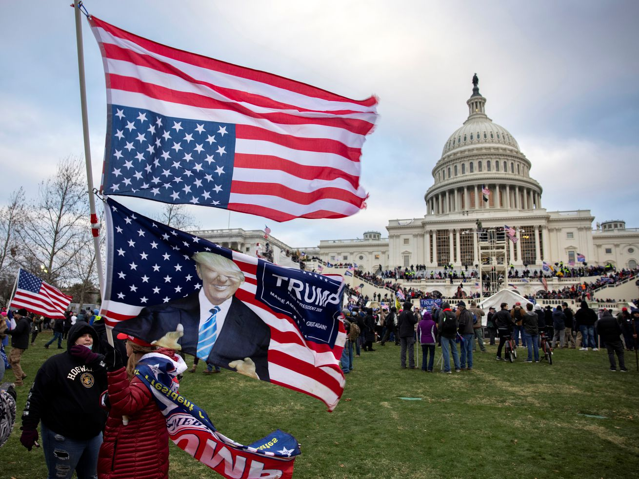 Protesters hold a Trump flag by the Capitol.