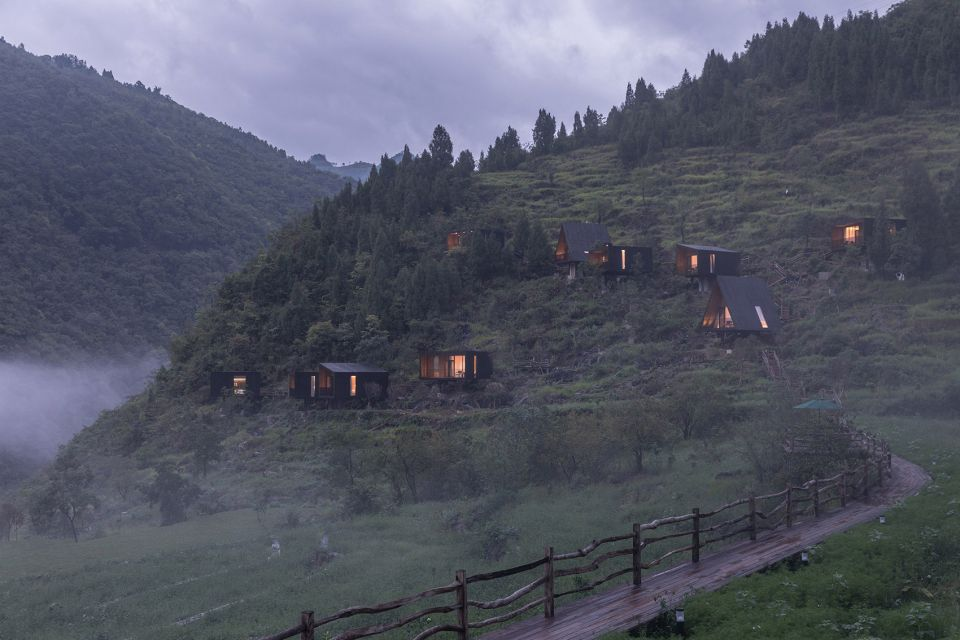 Cabins on a mountainside with light illuminating them from the inside. The cabins all have dark charred wood facades.