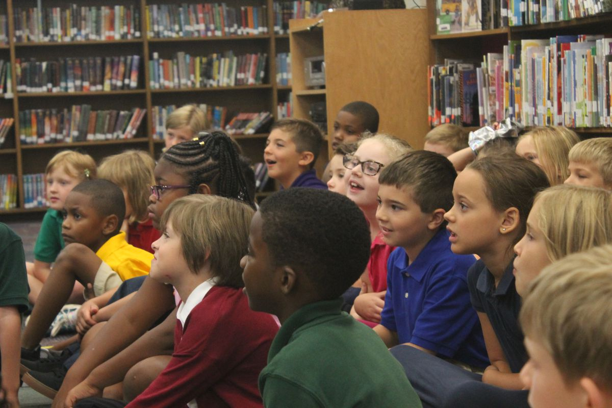 Second grade students listened attentively as Ferebee read a children's book in the school library.