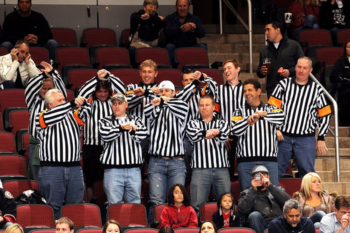 GLENDALE, AZ - MARCH 22: Phoenix Coyotes referees help the on-ice officials make a holding call on the St. Louis Blues on March 22, 2011 at Jobing.com Arena in Glendale, Arizona.  (Photo by Norm Hall/NHLI via Getty Images)