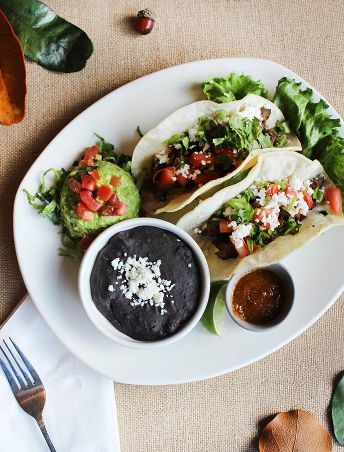 Two tacos plus guacamole and black beans on a large white plate from Kerbey Lane