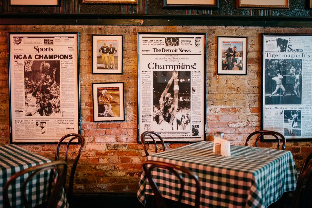 The inside of the bar shows championship newspapers hung on the brick wall. There are two dining tables with chair in front of the wall.