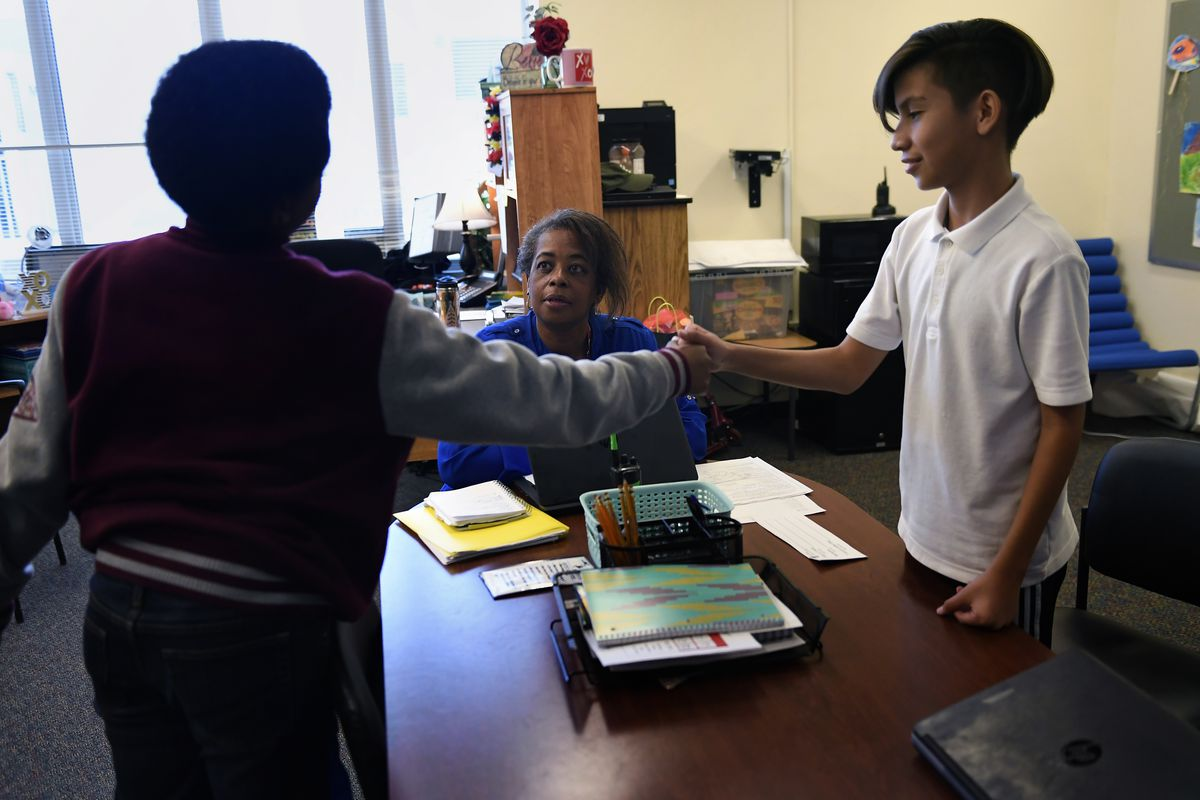 Sixth graders Jalon Ousley and Jorge Pacheco (right) shake after explaining their feelings and apologizing with Yvette Roaf-Bess, their restorative liaison at East Middle School in Aurora. (Photo by Joe Amon/The Denver Post)