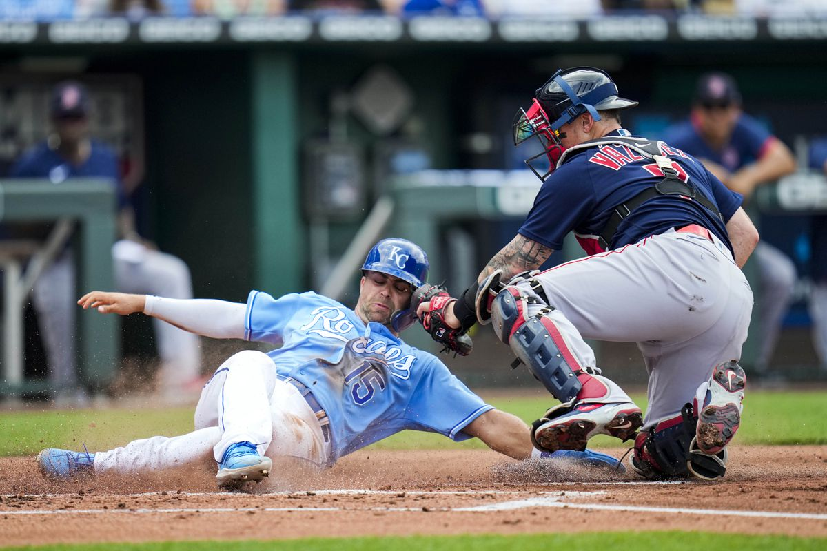 Kansas City Royals right fielder Whit Merrifield (15) is tagged out at home by Boston Red Sox catcher Christian Vazquez (7) during the first inning at Kauffman Stadium.