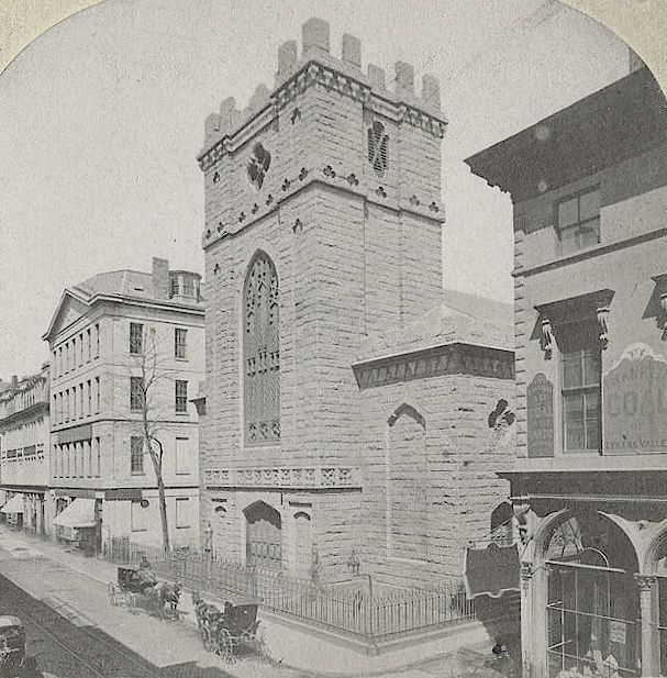 An old photograph of a small, castle-shaped church on a sidewalk.
