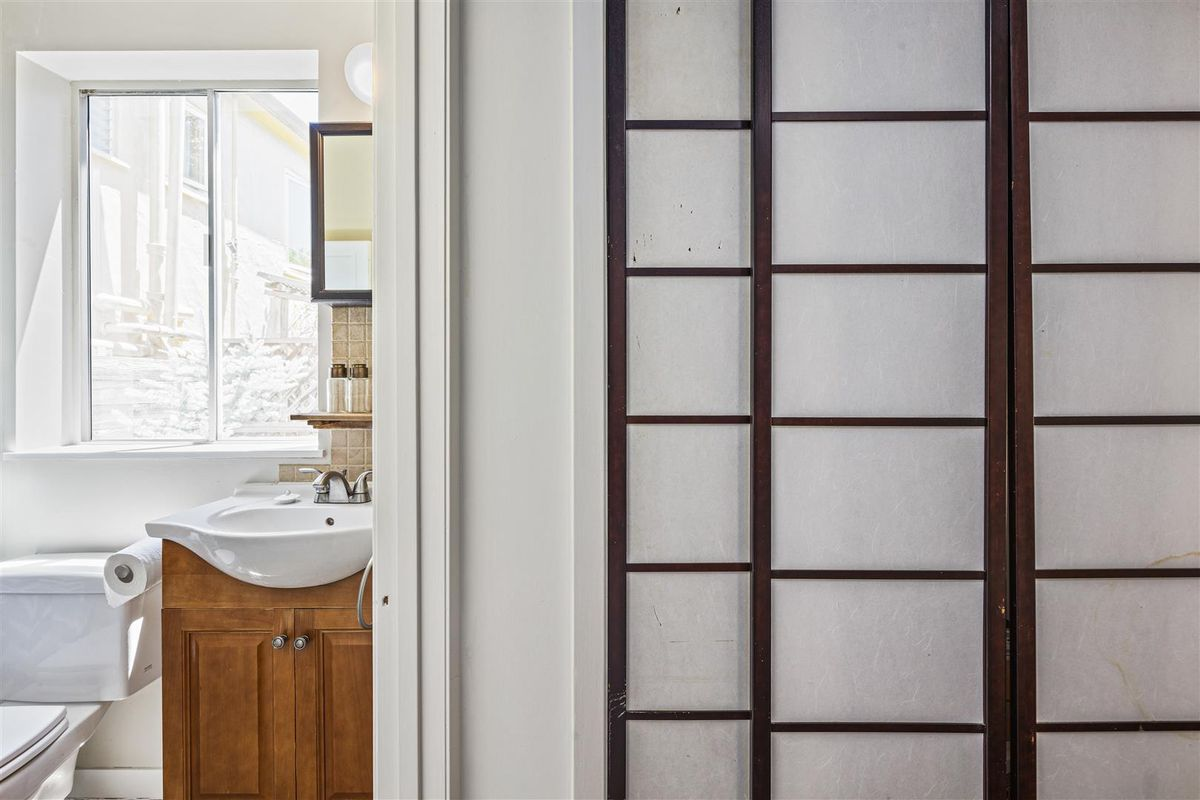 A head-on view of the bathroom and the closet screen door.