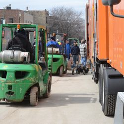 12:34 p.m. Forklifts lined up on Waveland to unload the Cubs gear truck -