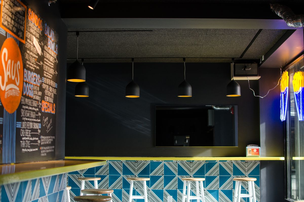 an interior shot of saus at bow market somerville, including a chalkboard menu and walls painted in a striking turquoise stripe pattern