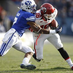 Utah wide receiver David Reed (16) runs upfield as Brigham Young defensive back Brian Logan (7) moves in for the tackle as Brigham Young University plays against Utah at LaVell Edwards Stadium in Provo, Utah, Saturday.