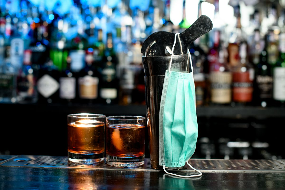 A cloth mask hangs on a cocktail mixer at a bar next to two brown-ish colored drinks.