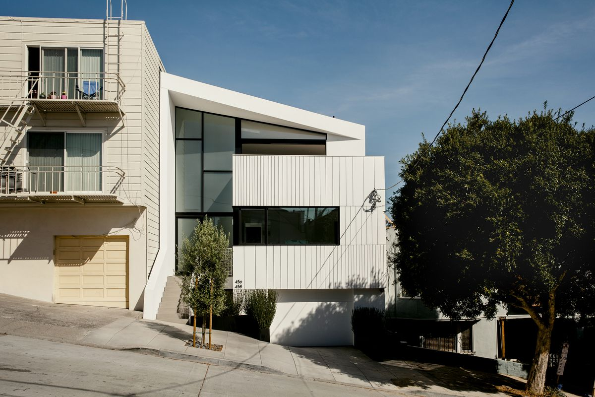 A white house built into a hill on a San Francisco street.