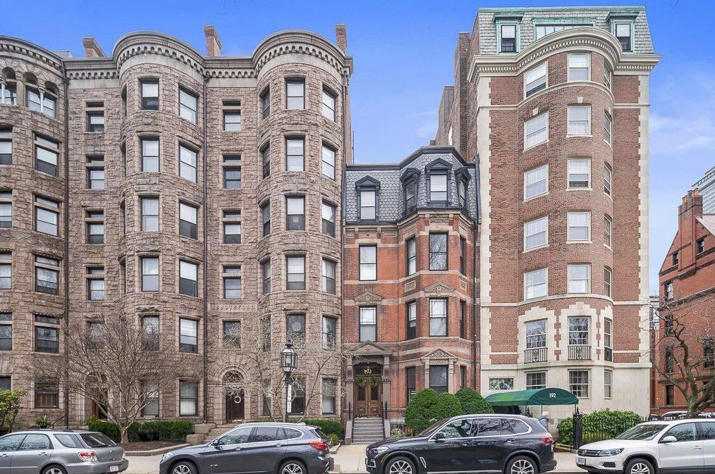 A four-story brownstone sandwiched between much taller buildings.